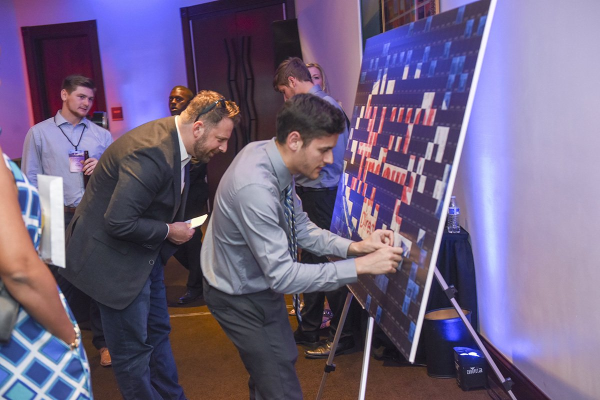 corporate events cleveland ohio | man taking off a sticker from the prize board at the universal windows direct event