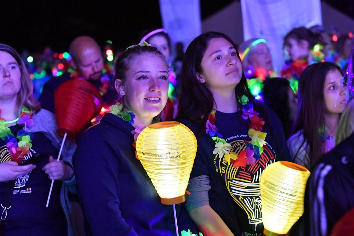event planners cleveland | smiling people holding lit lanterns at the 2018 light the night event