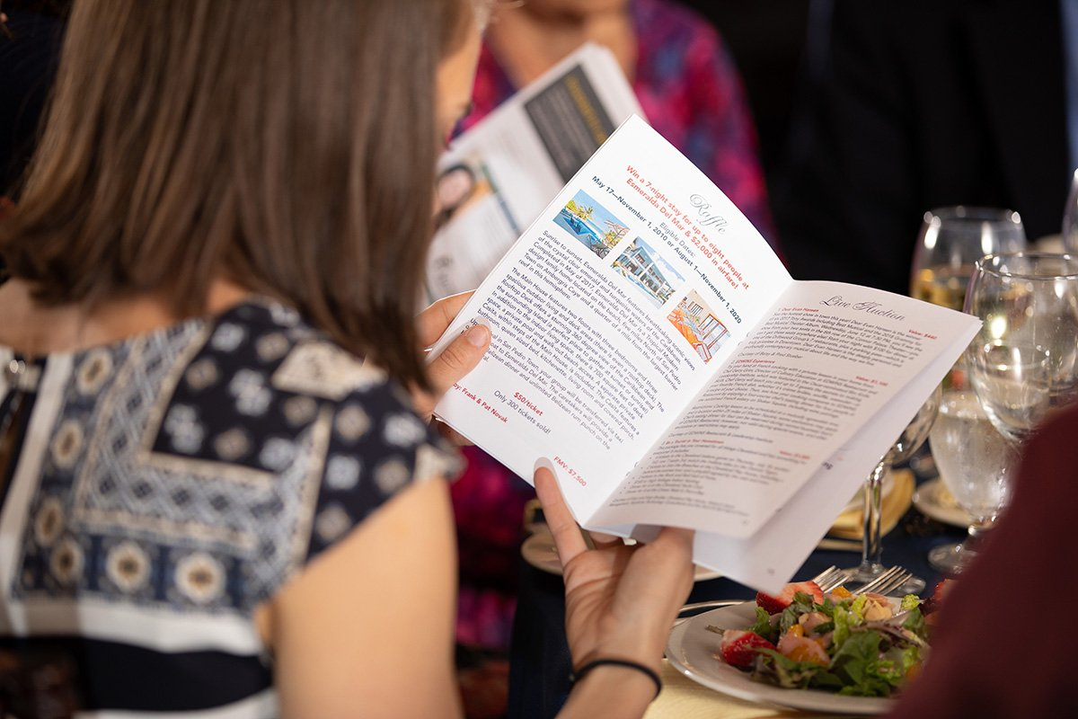 improve an annual fundraising event by simplifying | woman looking at brochure