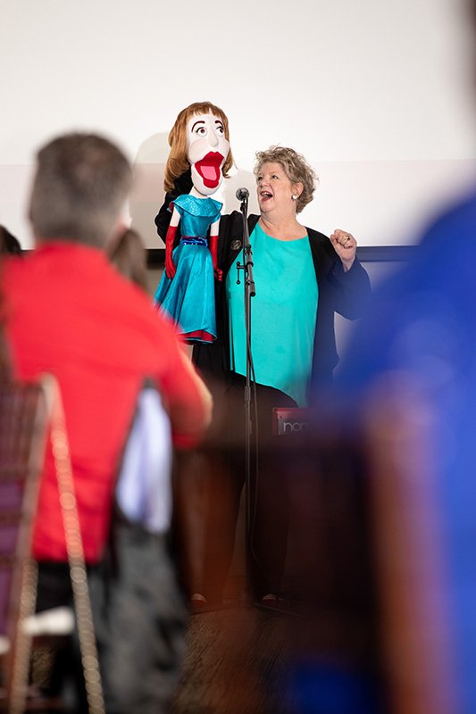 fundraising events cleveland ohio | woman and puppet singing into a microphone
