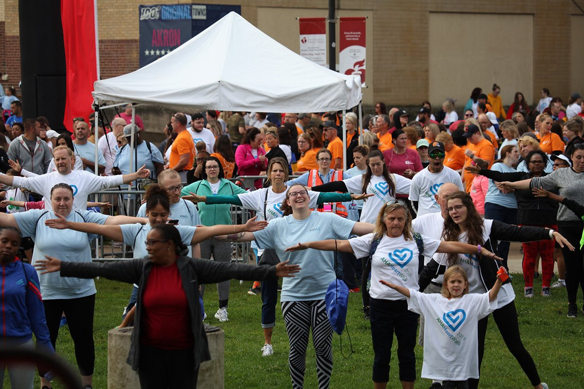 outdoor fundraising event | group people stretching in front of a white tent
