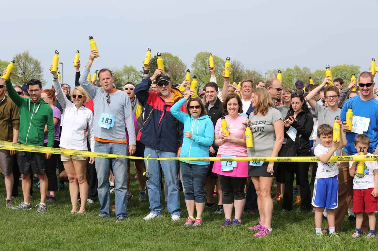 nonprofit event planning | group of people with water bottles on their heads at a finish line