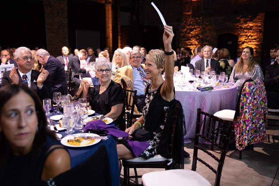event planning services | audience member raising her hand at dinner at the 2018 CHSC fall benefit
