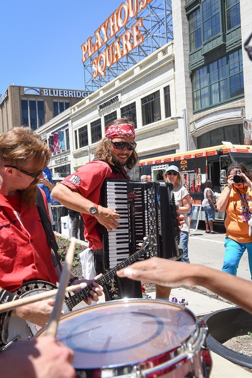planning an outdoor music festival drummer, guitarist and accordian player in front of playhouse square